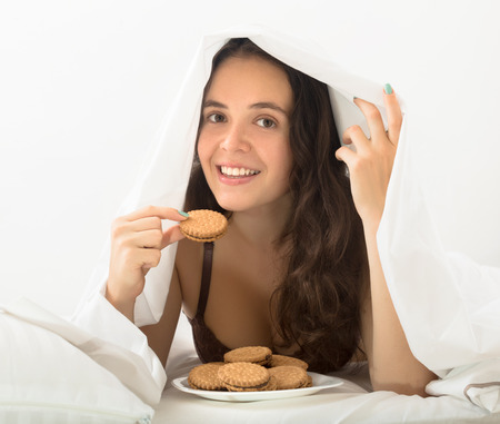 furtively: Long-haired woman eating sweet chocolate chip cookies in bed Stock Photo