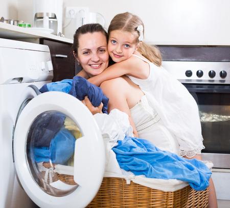 mujer ama de casa: sonriente ama de casa americana y su hija con ropa cerca de la lavadora Foto de archivo