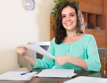 filling in: Cheerful young brunette long-haired woman filling in paper at home