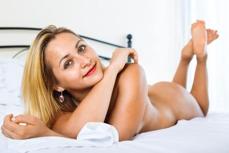 mujer desnuda sentada: Belleza joven mujer desnuda sentada en la cama en el dormitorio