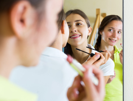 makeups: Adult beautiful woman making make-up near mirror. Focus on the left woman