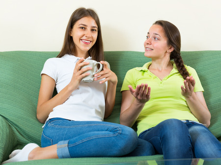 Happy smiling female friends talking to each other at home and drinking hot beverage