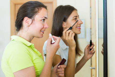 makeups: Young smiling girls doing make-up in front of the mirror at home