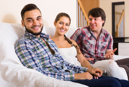 polygamy: Three happy adult partners in home interior