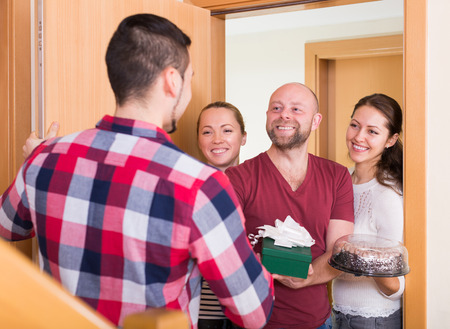 holiday gathering: Family couple receiving visitors with the gifts in home