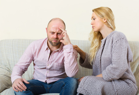 soothe: Sad man has problem, woman consoling him on sofa at home. Focus on men Stock Photo