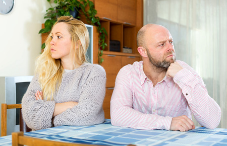 insult: Family quarrel. Sad man and woman during quarrel  in living room at home  couple having problems at home Stock Photo