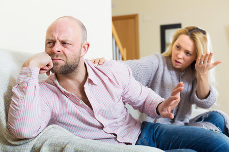 unhappy man: Casual family having quarrel in livingroom at home