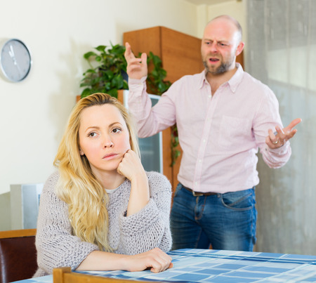 two woman: Angry guy and sad woman during quarrel at home Stock Photo