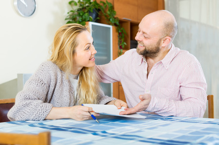 hypothec: Positive smiling couple discussing details of marriage settlement at home