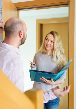 outreach: Man answer questions of outreach worker with paper in home door