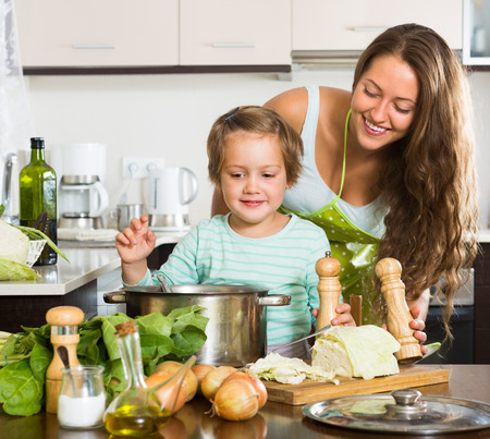 mother cooking: Young mother with little daughter cooking soup together at domestic kitchen. Focus on girl