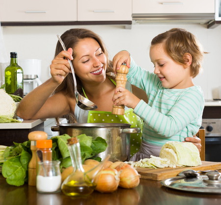 vegetable cook: Smiling young woman with baby cooking soup at home kitchen. Focus on woman