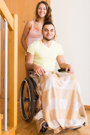 coming home: Positive young woman and her disabled husband in wheelchair coming home. Focus on man