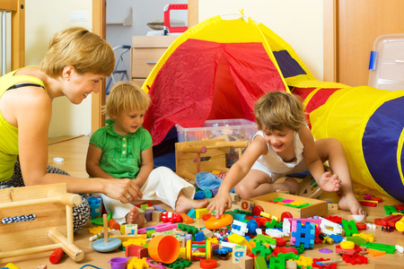 siblings: Woman and two siblings together playing with  toys in home
