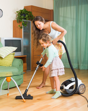 Young mother and little daughter are doing house cleaning. Focus on girl