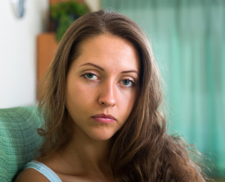 heartbreak issues: Close up portrait of sad young long-haired girl in home interior