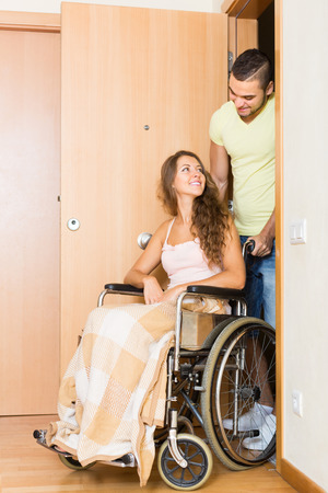 coming home: Handsome young man and his disabled wife in wheelchair coming home. Focus on woman Stock Photo