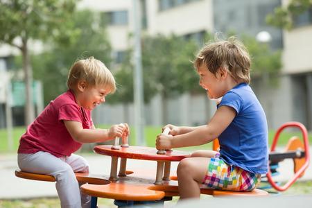 niños en recreo: Dos pequeñas hermanas felices jugando a bordo tambalea