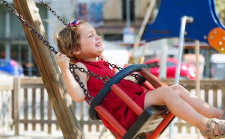 totter: child in red dres on chain swing in playground