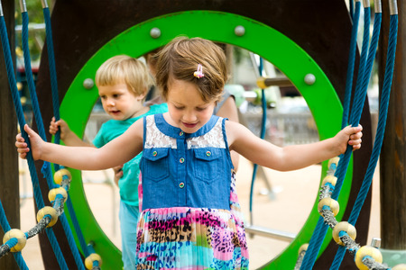kid's day: Two cute little sisters at action-oriented playground in park Stock Photo