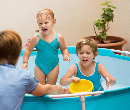 babysitter: Female baby-sitter with little girls at inflatable pool