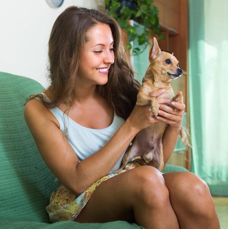 russkiy: Smiling female holding Russkiy Toy Terrier indoor