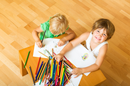 gladful: Two children together with pencils  at home