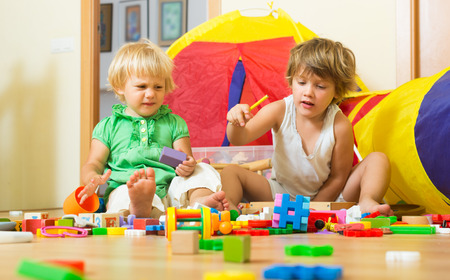 sad cute baby: Two calm little children playing with toys in home interior