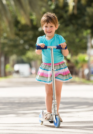 4 years old: 4 years old girl staying with scooter in park and smiling Stock Photo