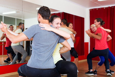dance: Smiling adults dancing bachata together in dance class