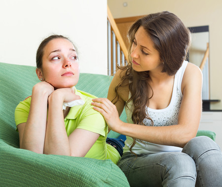 cognate: Young longhaired girl calms her upset crying friend