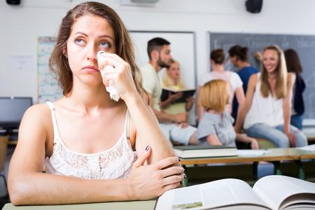 bulling: Ni�a llorando triste que se sienta en su escritorio solo en el aula de la universidad