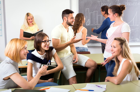 informal clothing: Group of students having informal conversation in classroom during a break