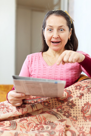 mirth: positive surprised mature woman looks newspaper at home