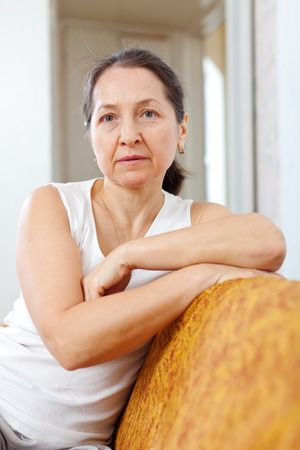 wistful: Portrait of  wistful beauty mature woman in home interior Stock Photo