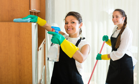 Two positive young females cleaning together in the room