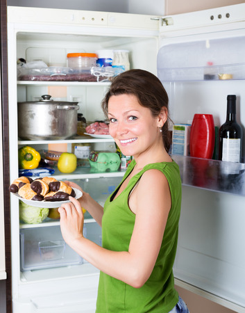 woman eating cake: Happy brunette woman eating cake from fridge  at home