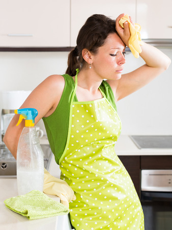 unsatisfactory: Unhappy woman cleaning furniture at domestic kitchen Stock Photo