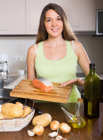 fryingpan: Smiling young housewife cooking salmon fish in frying pan at kitchen Stock Photo