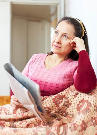 wistful: wistful mature woman reads newspaper at home