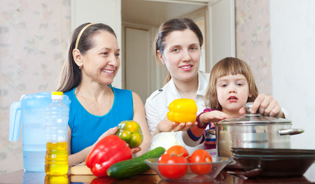 three generations of women: three generations of happy women cook vegetables in  kitchen at home