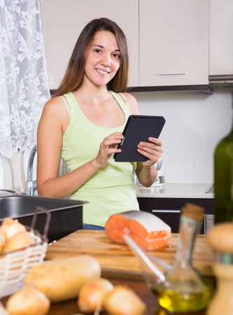 ereader: Smiling woman cooking salmon fish and reading  ereader at  kitchen