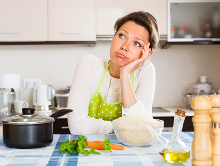Pensive woman cooks rice with vegetables at home