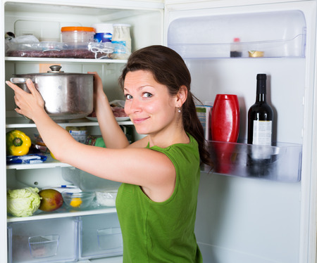 fridge: Hungry woman eating soup from pan near fridge  at kitchen Stock Photo