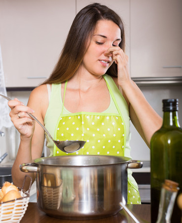 pinched: Young housewife in apron pinched her nose avoiding bad smell from pan