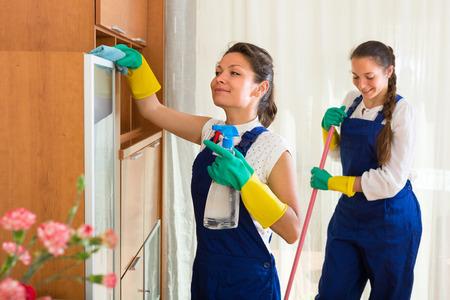 maid: Profesional sonriente equipo de limpieza en la casa con trapos y limpiadores de la fregona. Enfoque selectivo