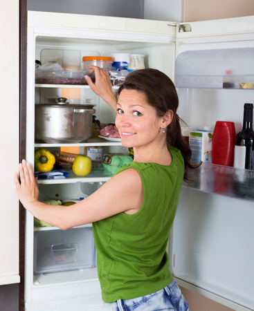 starving: Positive brunette woman searching for something in refrigerator  at home