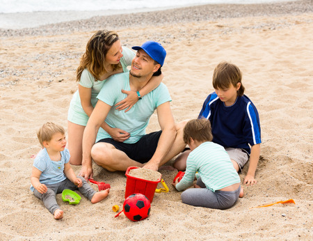 family vacations: Happy parents with children sitting on sea coast