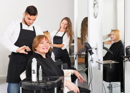 fodrászat: Portré pozitív mosolygós idősebb nő vágás haját a fodrász szalon Stock fotó
